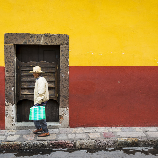 """""""San Miguel de Allende, Mexico - May 29, 2014: Man passing in front of a door in the historic center of the city of San Miguel de Allende, Mexico."""" stock image"""