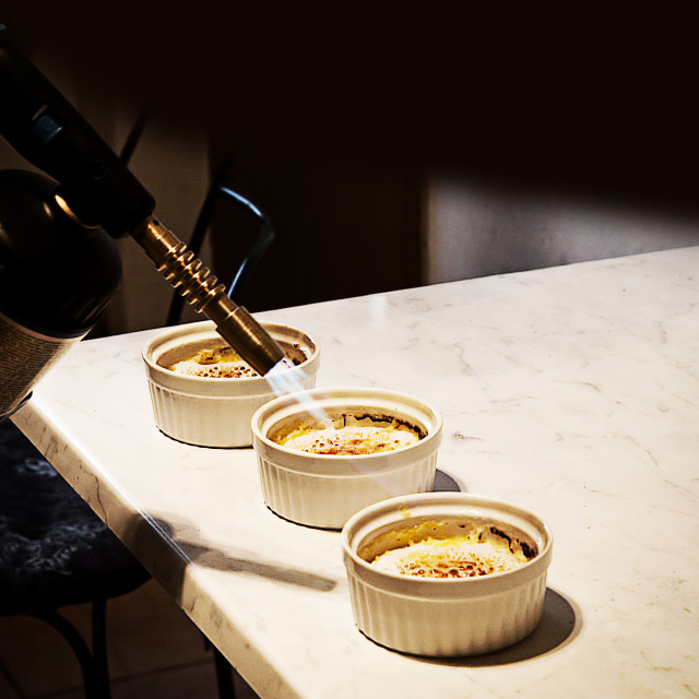 """Creme brulee final incrustation preparation in the kitchen"" stock image"