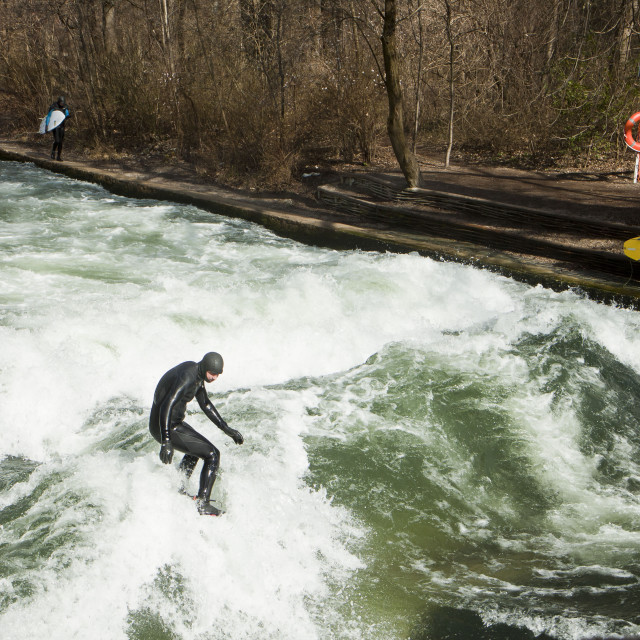 """Winter surfing in diving suit on the Eisbach river at Englischer Garden in..."" stock image"