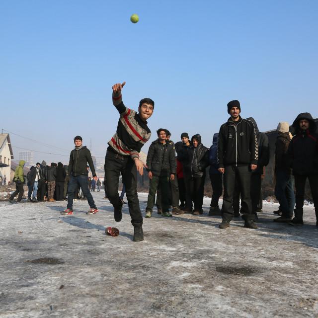 """Refugees play cricket outside warehouse"" stock image"