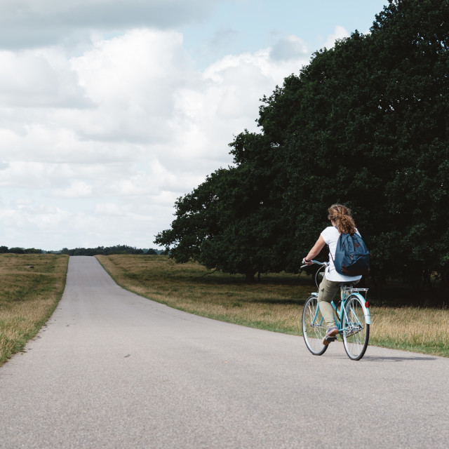 """Smiling pretty young woman riding bike in a country road in the"" stock image"