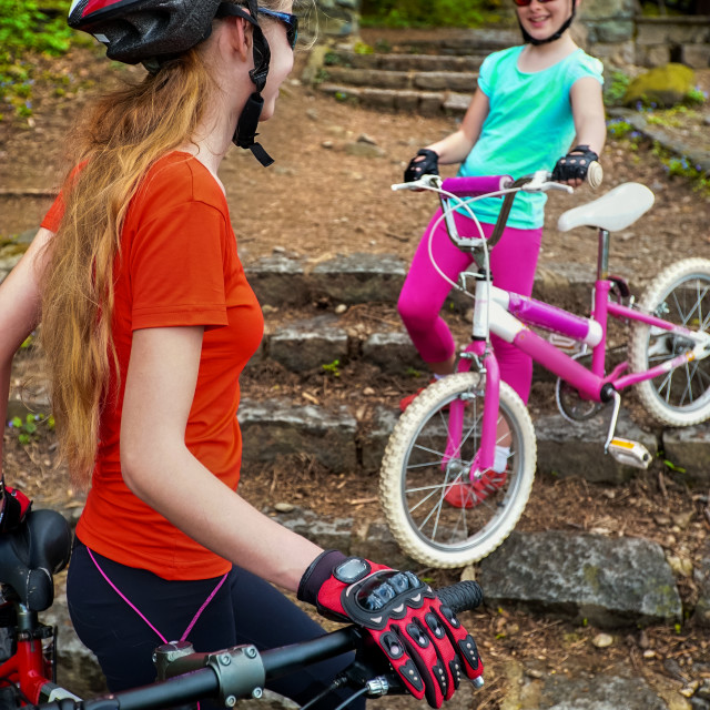"""""""Bicyclist child ride on bicycle path in city. Children go down stairs in park."""" stock image"""