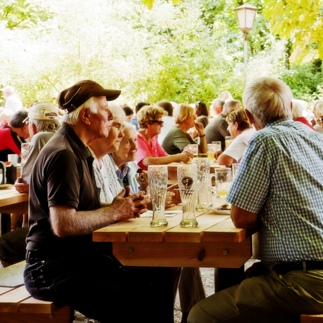 """People seat and drink leasurely outside at one of the numerous beer gardens..."" stock image"