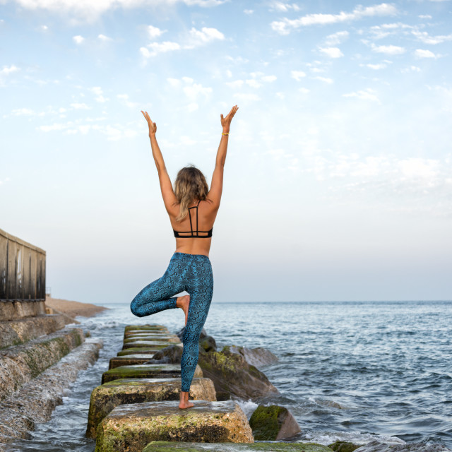 """woman practicing yoga by the sea standing on rocks"" stock image"