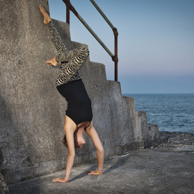 """woman doing a handstand against a wall by the sea"" stock image"