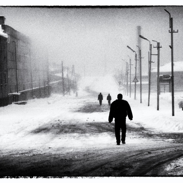 """Sevan Armenia A figure walks through the winters snow, film noire effect."" stock image"