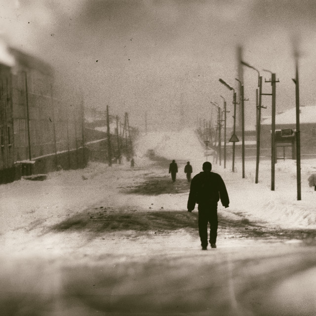 """Sevan Armenia A figure walks through the winters snow, old film effect."" stock image"