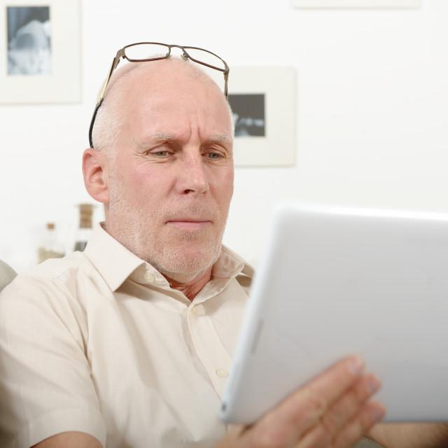 """mature man having eyesight problems, he using tablet"" stock image"