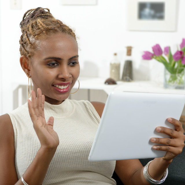 """Multi-ethnic woman talking online with tablet"" stock image"