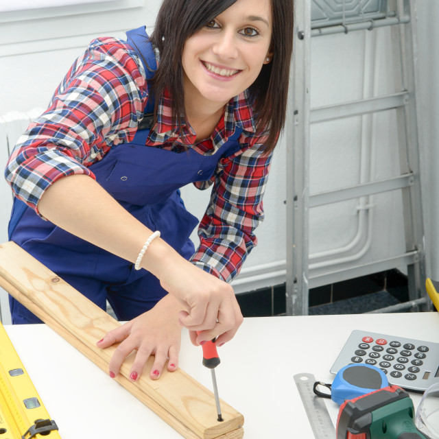 """smiling woman assembling wooden planks using screwdriver"" stock image"