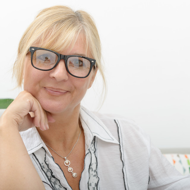 """Portrait of mature woman sitting on sofa"" stock image"