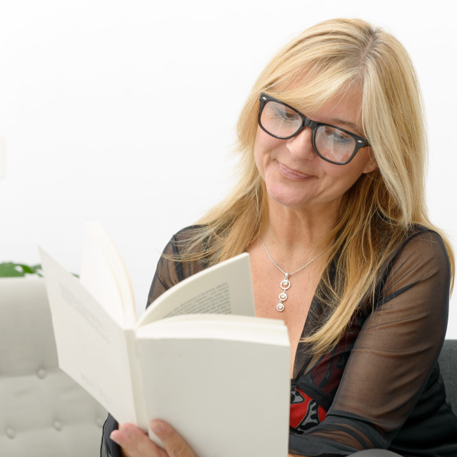 """""""mature blond woman reading a book"""" stock image"""