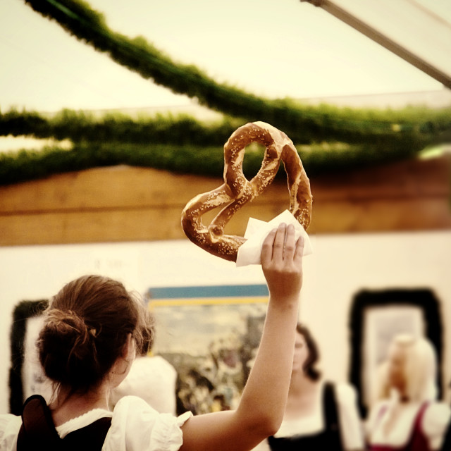 """waitres selling big traditional pretzels at an Oktoberfest kiosk in Munich"" stock image"