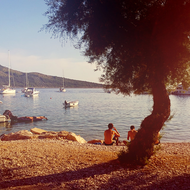 """Primosten, Croatia - tourists on strand at sunset"" stock image"
