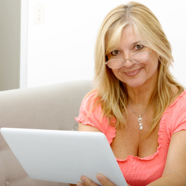 """""""Beautiful mature woman using electronic tablet at home"""" stock image"""