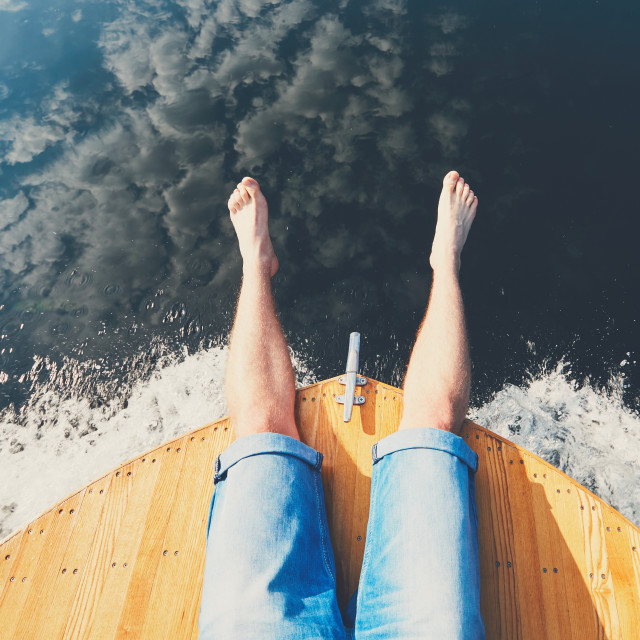 """Summer relaxation on the river. The legs of a man sitting on the bow of the boat."" stock image"