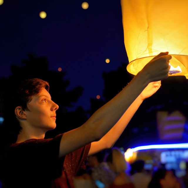 """Teen boy with paper flying lanterns"" stock image"