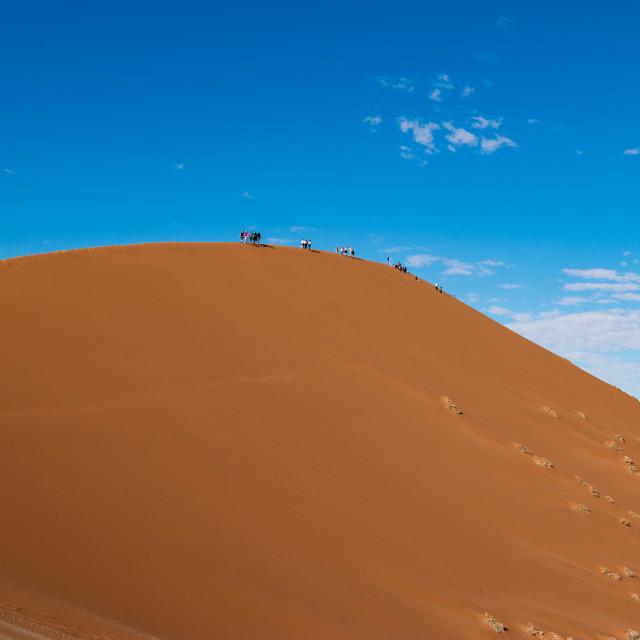"""Tourists on sand dune in Sossuvlei, Namibia"" stock image"