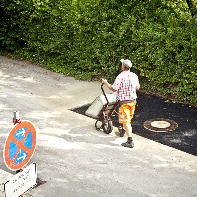 """""""worker walks to the bitumen truck to refill his barrow to finish asphalting a..."""" stock image"""