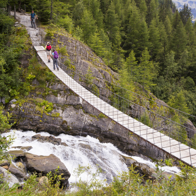 """Walkers on the Tour Du Mont Blanc cross a suspension bridge across the..."" stock image"