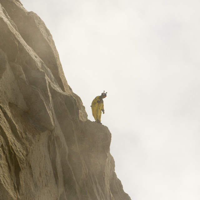 """A base jumpers wearing a wing suite prepares to jump from the Aiguille Du..."" stock image"