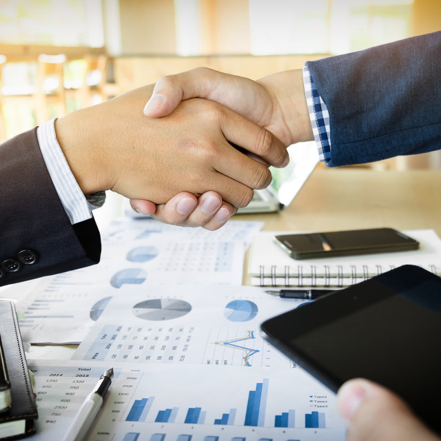 """""""Businessmen shaking hands during a meeting"""" stock image"""