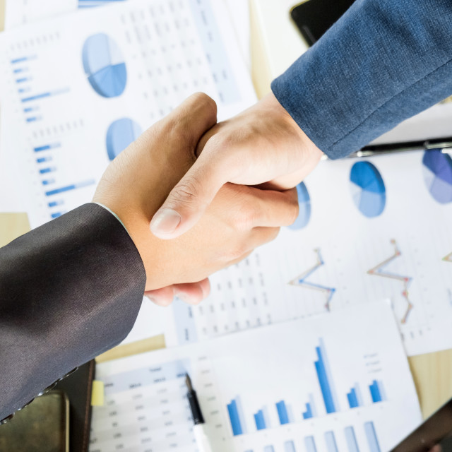 """Businessmen shaking hands during a meeting"" stock image"
