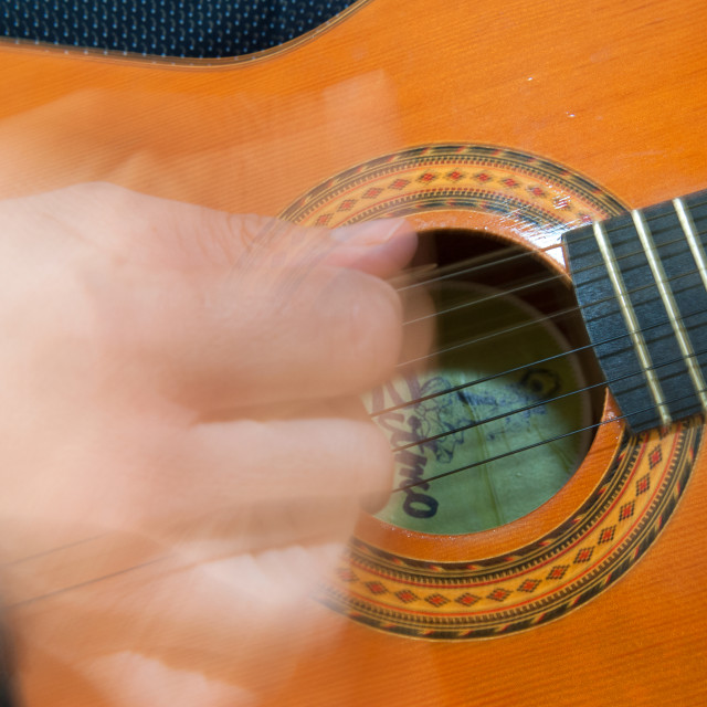 """Man strumming on a guitar"" stock image"