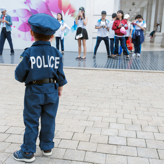 """""""Ho Chi Minh City / HCMC / Saigon Vietnam A toddler wearing a police uniform gets the attention of passing teenagers."""" stock image"""