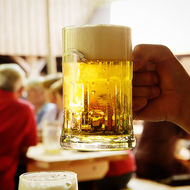 """Drinking beer in one of the many open air restaurant called ""Biergarten""..."" stock image"