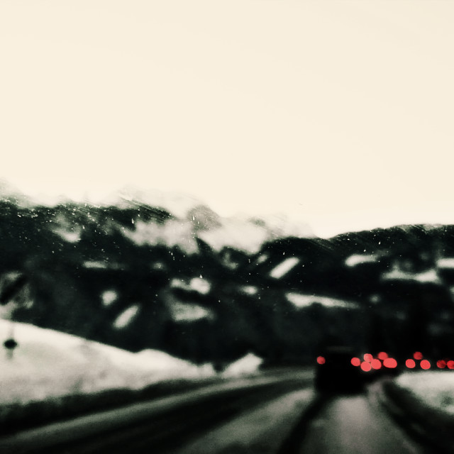 """Snowy blurred landscape on mountain road with stormy weather"" stock image"