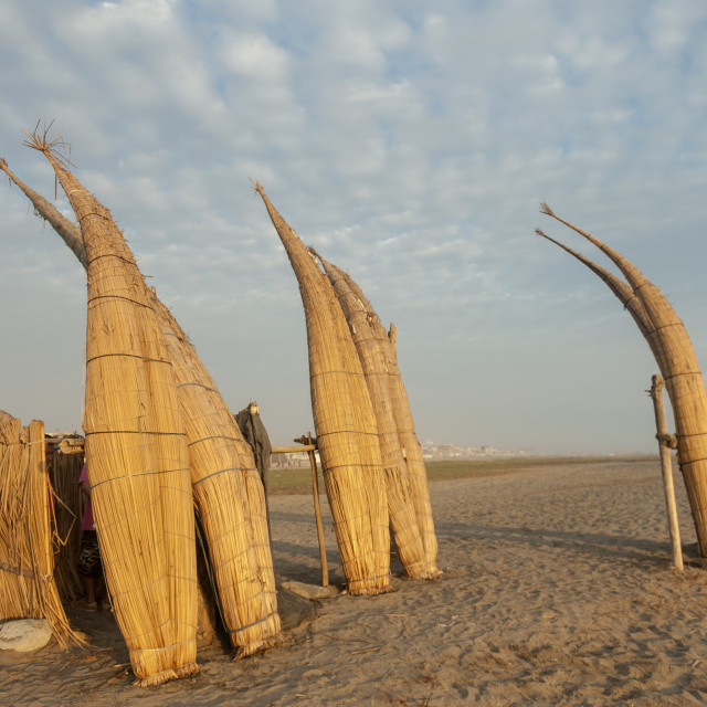 """Huanchaco Peru Two ""Caballitos de totora"" stand on their ends silhouetted near the Pacific Ocean. Caballitos de totora are traditional reed craft believed to have been used by Peruvian fisherman for the past three millenia."" stock image"