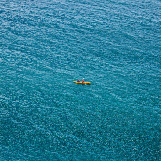 """Alone couple in kayak swimm through calm blue sea"" stock image"
