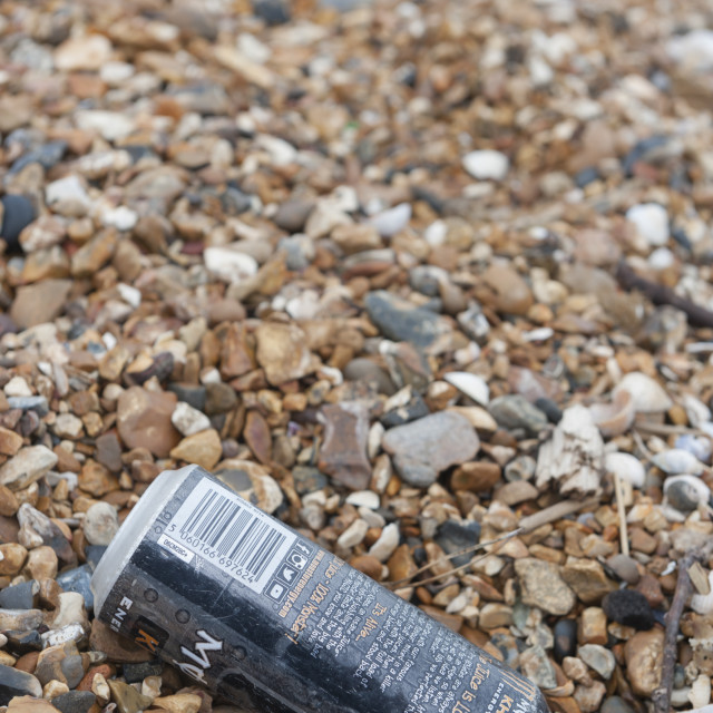 """""""Monster Khaos energy drink can thrown away and on the tide line of a UK shore. Not giving enough energy to walk to a bin 20 meters away."""" stock image"""