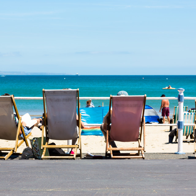 """Real people resting on deckchairs by promenade to Weymouth"" stock image"