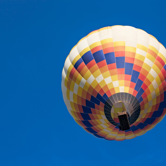 """Colorful hot-air balloon in flight seen from below"" stock image"