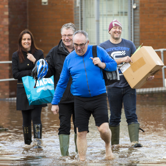 """""""The irony of the t shirt. Carlisle Rugby Club members wade through the flood..."""" stock image"""