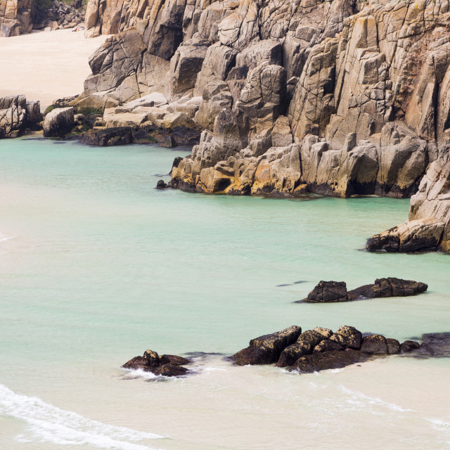 """The Granite cliffs of Porthcurno with sandy beaches mid tide."" stock image"