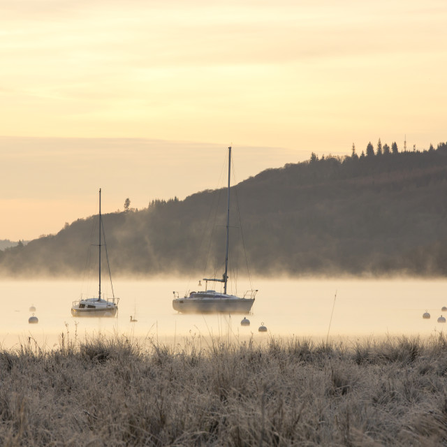"""Mist over Lake Windermere in Ambleside at dawn, Lake District, UK."" stock image"