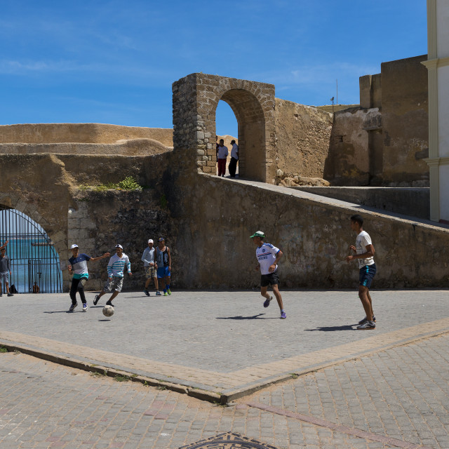 """El Jadida, Morocco - April 16, 2016: Young man playing soccer in a square close to the walls of the fortress of the Portuguese City (Cite Portugaise) in the town of El Jadida in the Atlantic Coast of Morocco."" stock image"