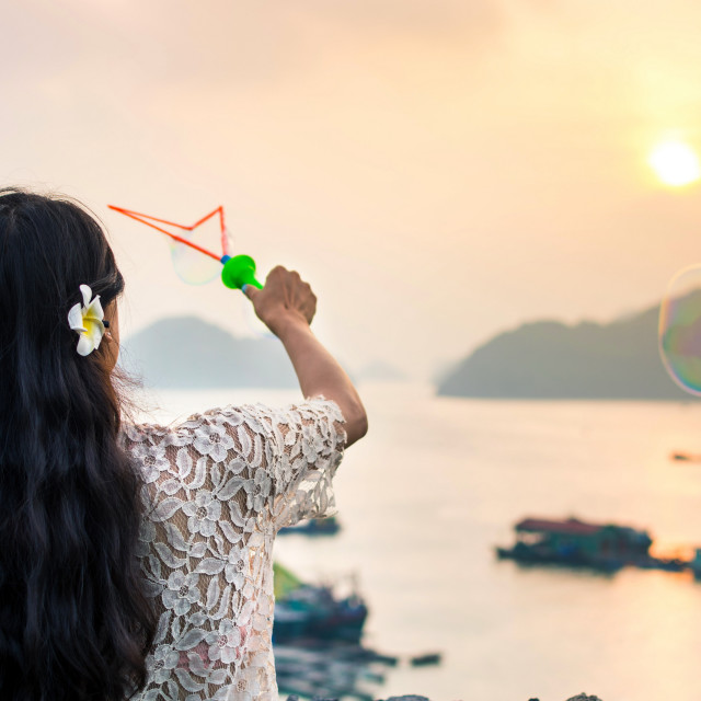 """""""Girl making soap bubbles on seaside at sunset"""" stock image"""