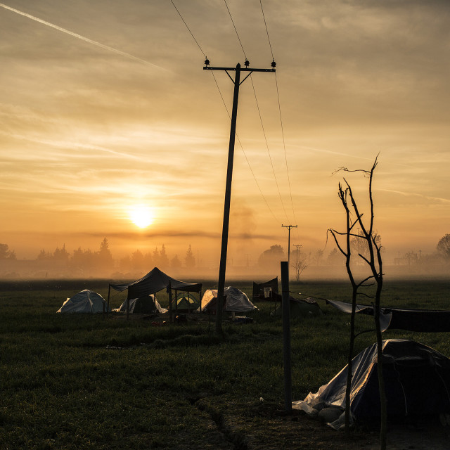 """Sun rises at the outskirts of the Idomeni makleshift refugee camp near the Fyrom border."" stock image"