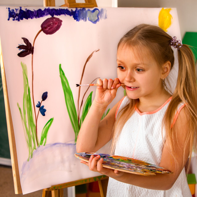 """""""Child painting finger on easel. Group of kids with teacher."""" stock image"""