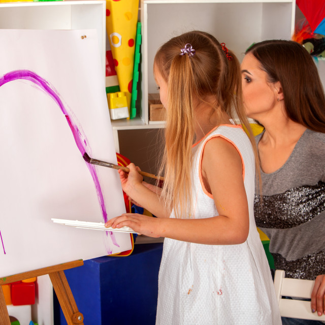 """""""Children painting brush on easel. Group of kids with teacher."""" stock image"""