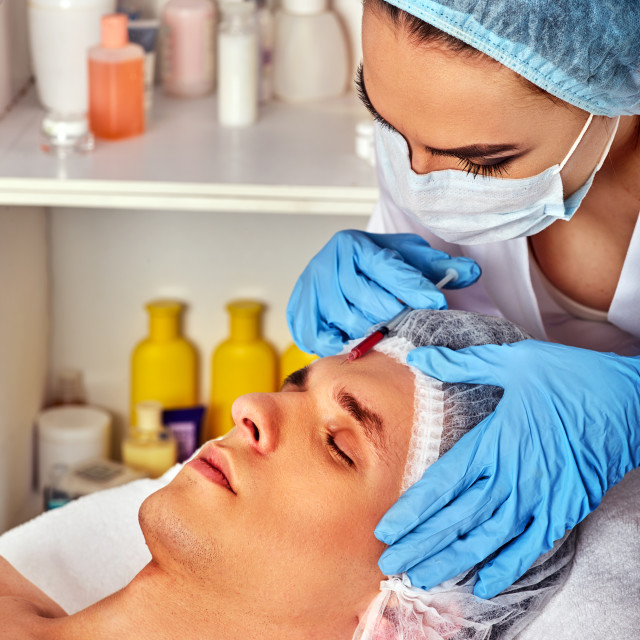 """""""Dermal fillers of man in spa salon with beautician."""" stock image"""