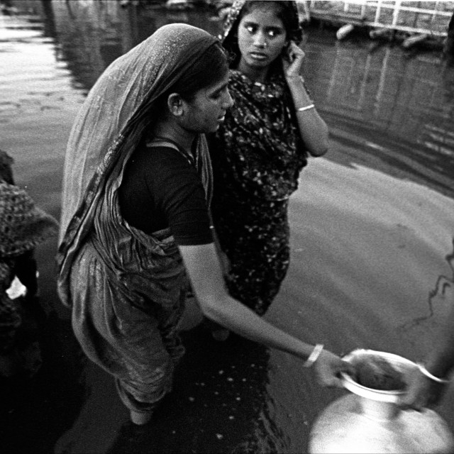 """Slum dwellers collecting drinking water from a tubewell submerged in..."" stock image"