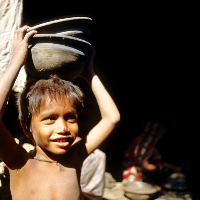 """A smiley child carries some potteries. Colourful earthenware like pots, jars,..."" stock image"