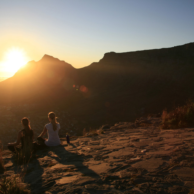"""women meditatiing at sunrise on top of Lions Head with Table Mountain in the..."" stock image"