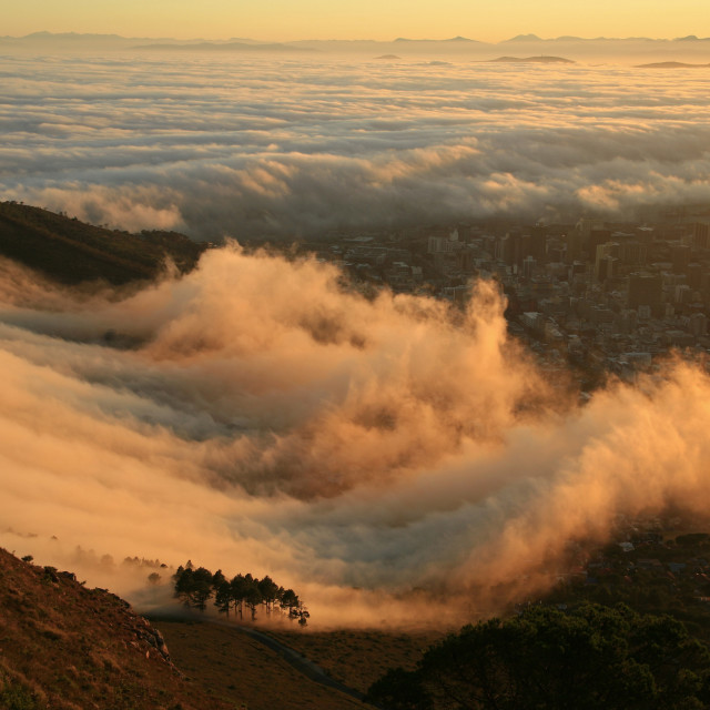 """mist bank rolls in at sunrise over Signal Hill and the city of Cape Town,..."" stock image"