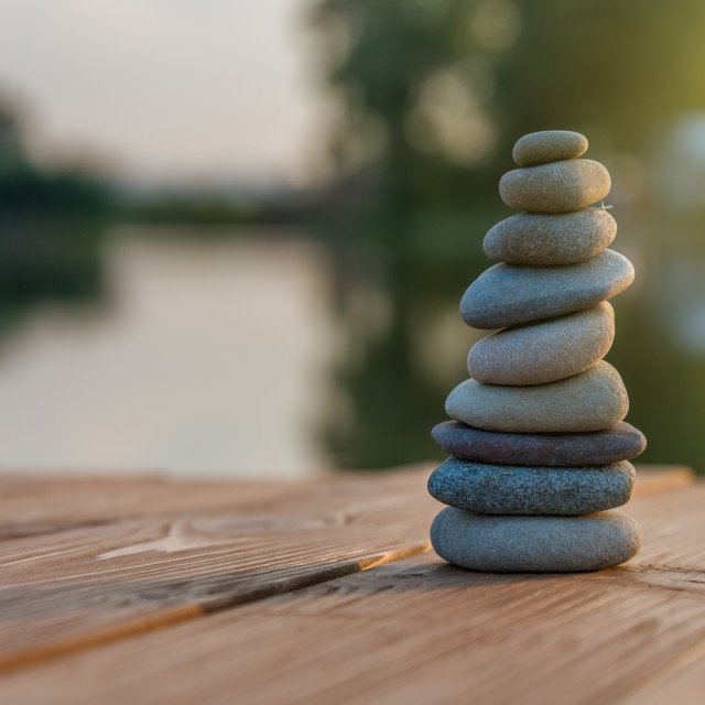 """Zen Balancing Pebbles Next to a Misty Lake"" stock image"
